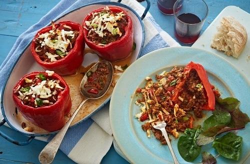 Plněné papriky po řecku, sypané sýrem a podávané s čerstvým chlebem.