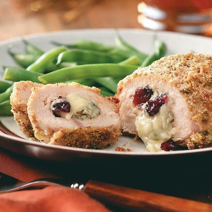 kuřecí řízek plněný zrajícím sýrem a brusinkami na talíři se zelenými fazolkami.