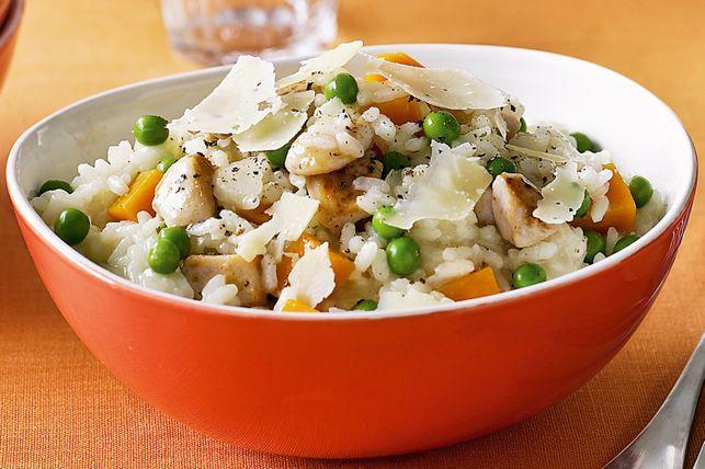 Červená miska s rýží, kuřecím masem, hráškem, dýní a parmezánem