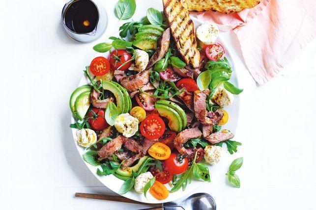 Talíř s listy salátu, s rajčaty, kousky avokáda a plátky masa