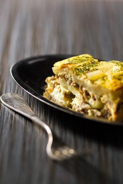Zapečené brambory na způsob řecké musaky s mletým masem, zdobené sušenou zeleninou a servírované na černém talířku.