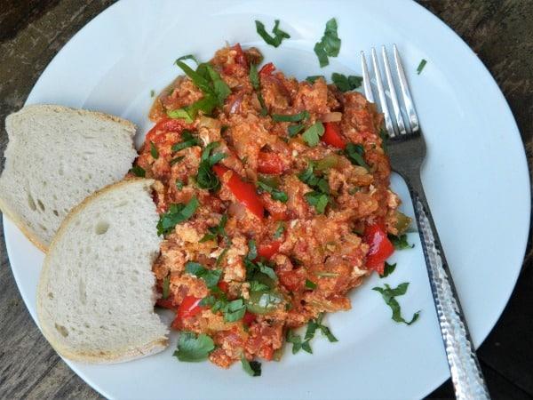Směs vařených vajíček, paprik a rajčat servírovaná s pečivem
