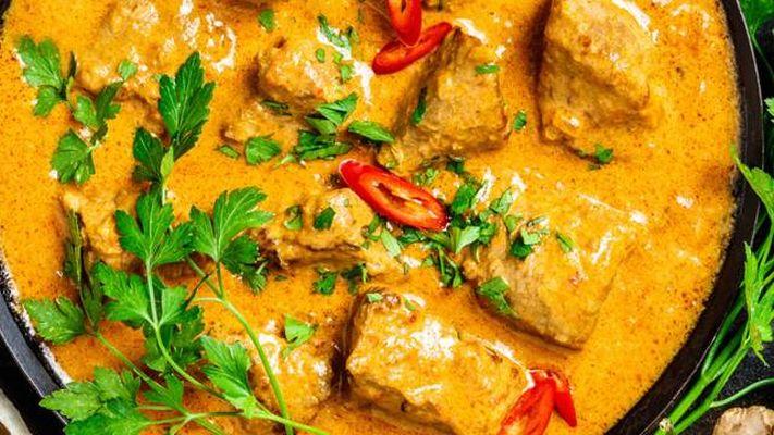 Asijský pokrm s kari a kousky krutího masa ozdobený čerstvým koriandrem