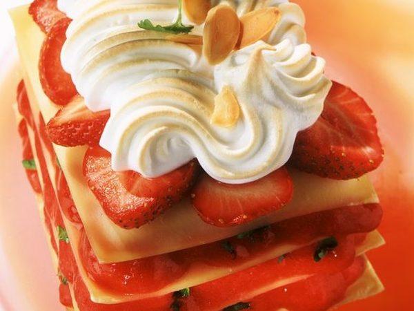 Jahodové lasagne ozdobené šlehačkou a plátky mandlí