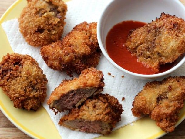 Pokrm z jater obalených v trojobalu podávaný s pikantní omáčkou