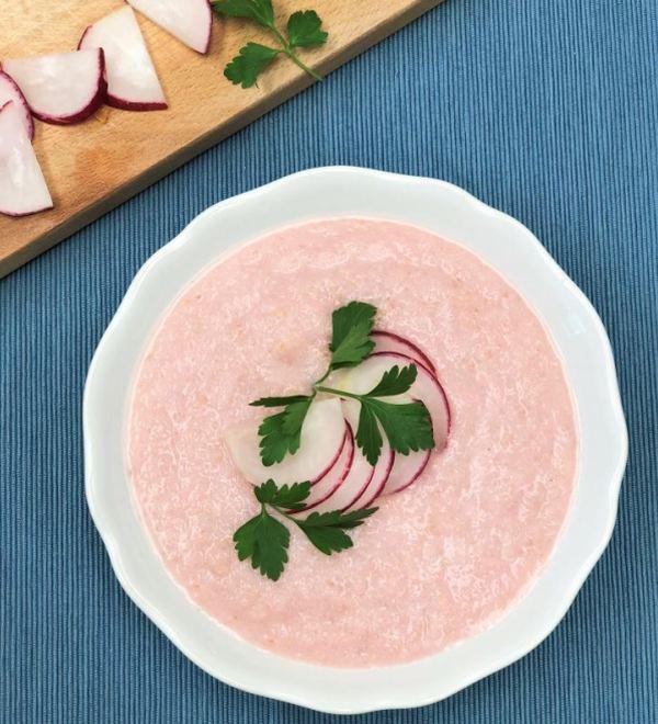 Růžová polévka s ředkvičkami ozdobená čerstvou petrželkou