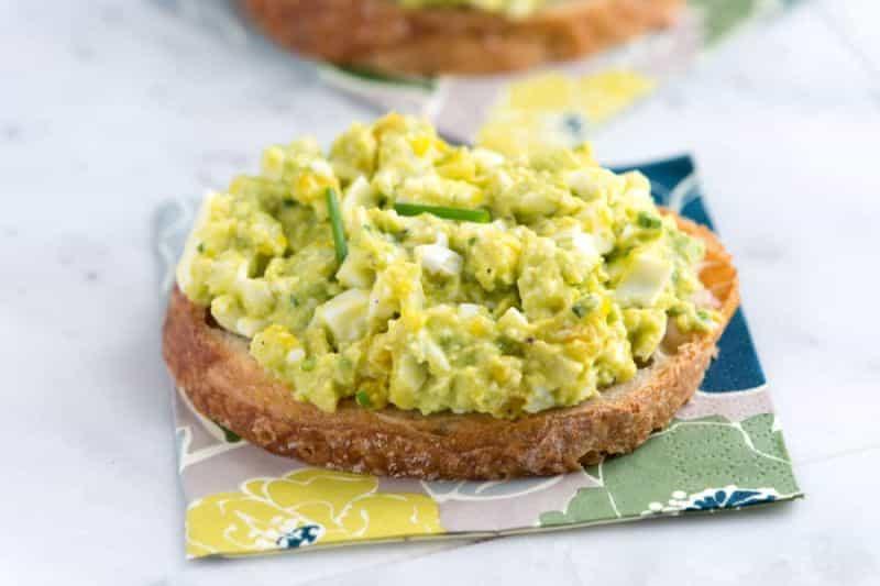 Krajíc chleba potřený pomazánkou vyrobenou z avokáda a vajec