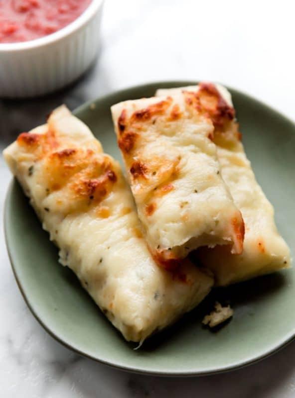 Slané tyčinky s mozzarellou servírované na talířku