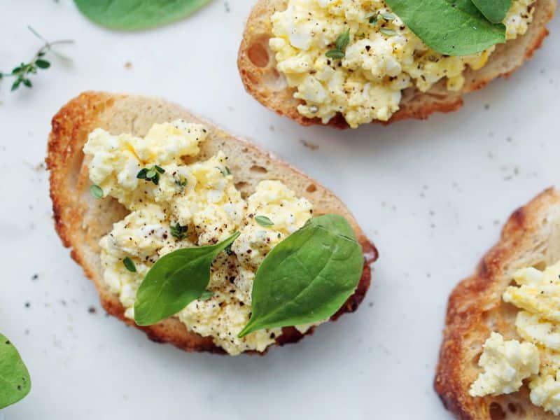 Opečené plátky pečiva potřené směsí vajíček, tvarohu a bylinek