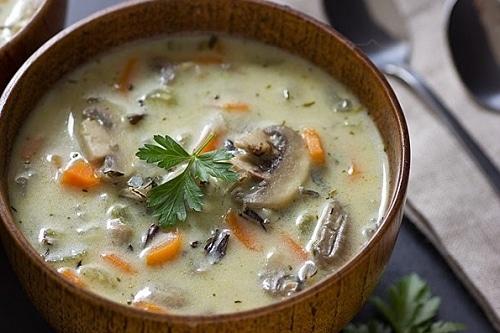 Zeleninová polévka s houbami, ochucená smetanou a zdobená petrželkou.