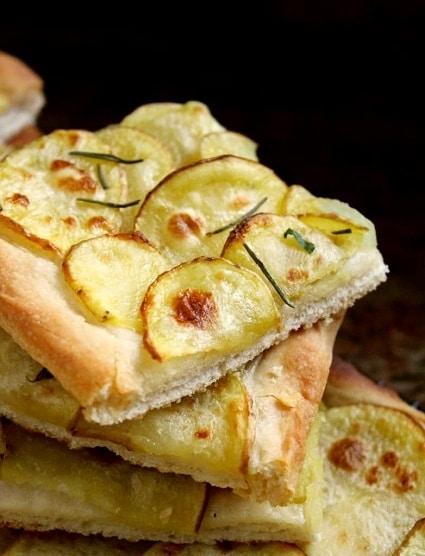 Těsto s brambory, nakrájenými na kolečka, sypané rozmarýnem.