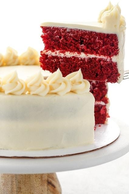 Pečený dezert s červenou náplní, zdobený bílou polevou.