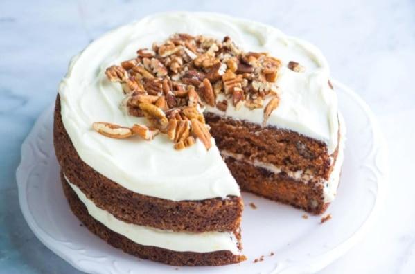 Pečený koláč s polevou z mascarpone, zdobený ořechy.