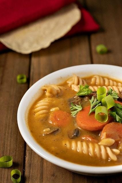 Těstovinová polévka z hub a zeleniny, zdobená čerstvou petrželkou a jarní cibulkou.