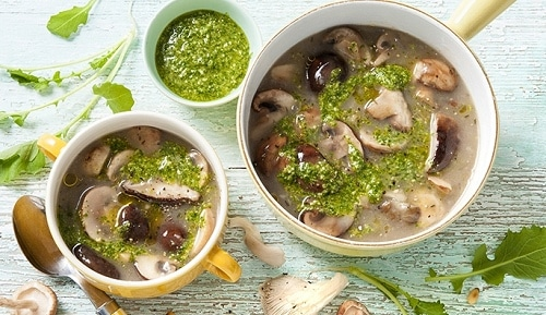 Hřibová polévka, podávaná s bylinkovým pestem.