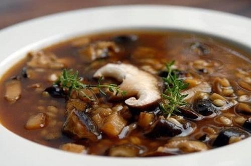 Tmavě hnědá houbová polévka s fazolkami, zdobená čerstvými větvičkami rozmarýnu.