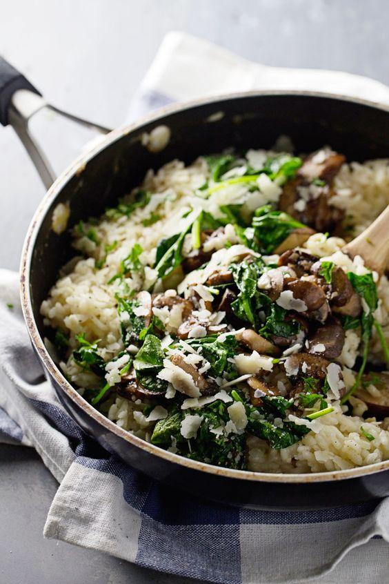 Krémová rýže s houbami, špenátem a posypaná parmezánem.