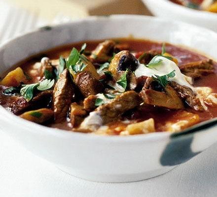 Hovězí guláš s bramborami, jogurtem a petrželkou v hlubokém talíři.