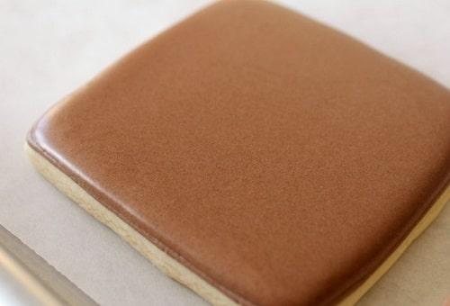 Čokoládová poleva na perníku ve tvaru čtverce.