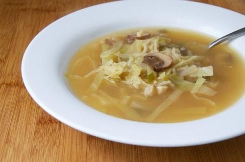 Kapustová polévka s houbami, servírovaná v bílém talíři.