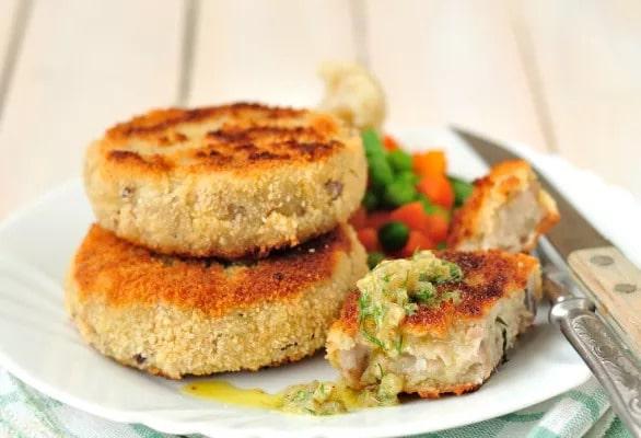 Kapustové placky na talíři se zeleninou a příborem.