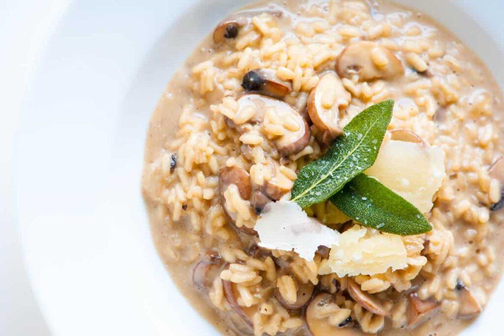 Smetanové risotto z hub, ozdobené šalvějem a parmezánem.