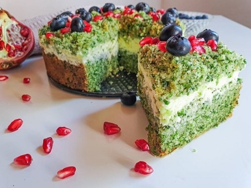 Zelený kulatý pečený koláč, zdobený borůvkami a zrnky z granátového jablka.