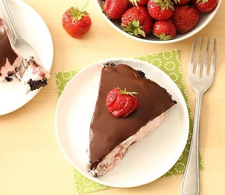 Jahodový kousek dezertu s čokoládovou polevou.