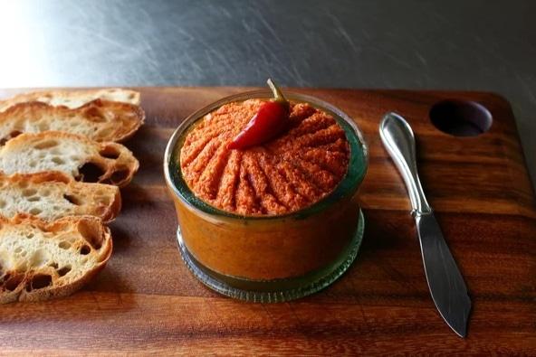 Sklenice plněná pikantním pomazánkovým pyré, zdobeným chilli papričkou a podávaným s topinkami.