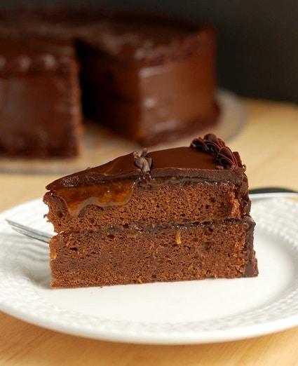 Kakaový kousek dortu, zdobený meruňkovým sirupem a čokoládovou polevou.