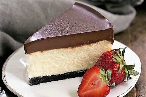 Tvarohový kousek dezertu s čokoládovou polevou, podávaný s čerstvými jahodami.