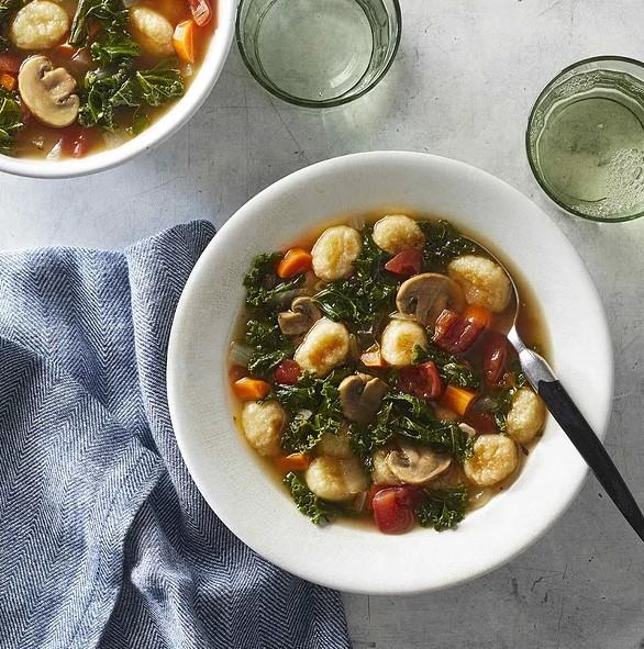 zeleninová polévka s gnocchi s houbami, rajčaty a mrkví v bílé misce se lžičkou