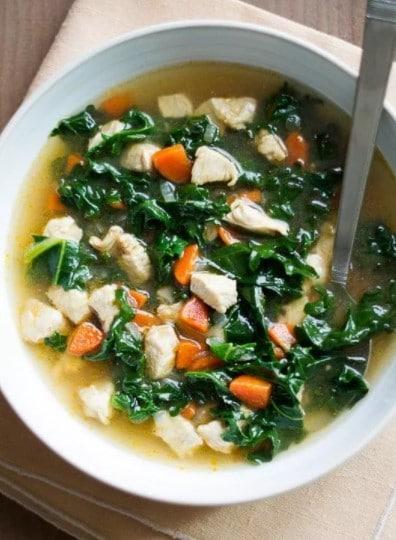 polévka s kuřetem a zeleninou v  bílé misce se lžičkou
