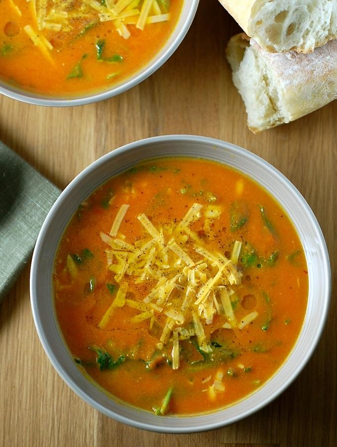 Mrkvová polévka se v misce se zeleninou a se strouhaným sýrem nahoře