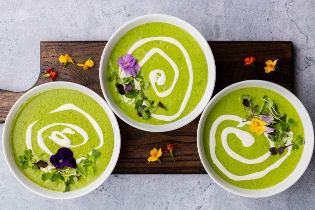 Misky se svěže zeleným kopřivovým krémem, ozdobené bylinkami a květy