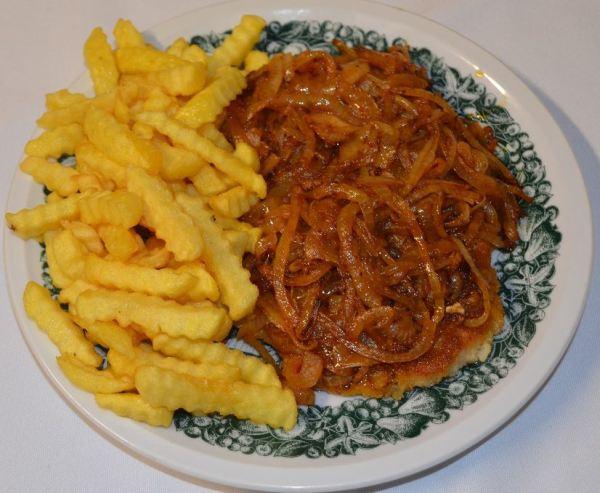 Řízek se slaninou, česnekem a cibulí servírovaný s hranolky