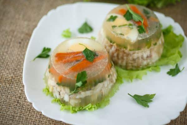 Kousky ryby se zelennou a vejci podávané v aspikovém přelivu