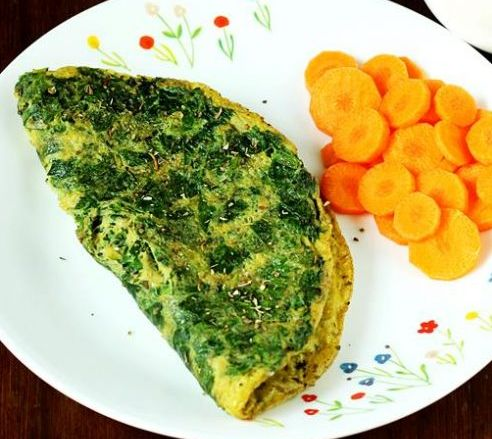 Špenátová omeleta podávaná s dušenou mrkví