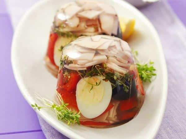 lahůdka v aspiku připravená z vajec, šunky, oliv, mrkve a papriky