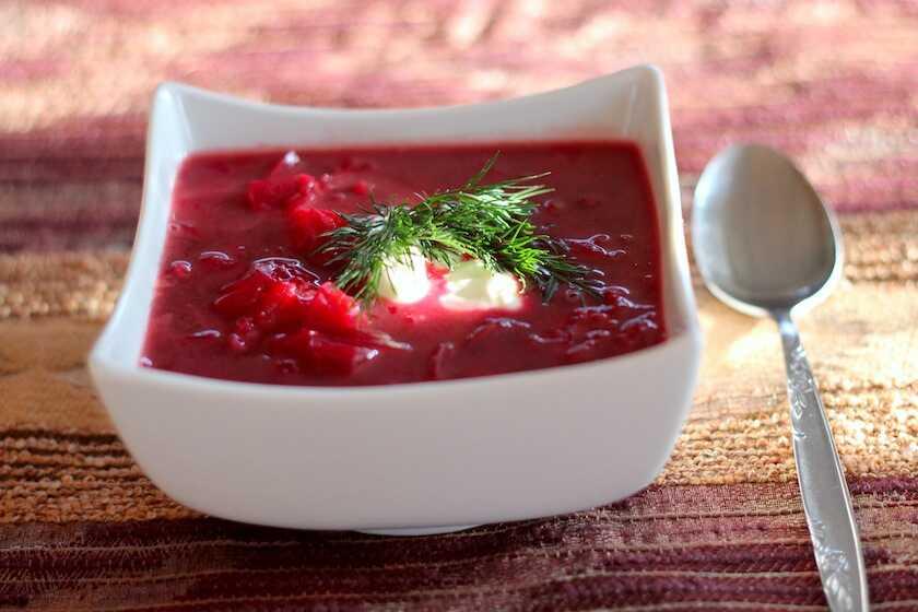 Polévka z řepy a kysaného zelí s kopečkem zakysané smetany a čerstvým koprem v servírovací misce s vedle položenou lžící.