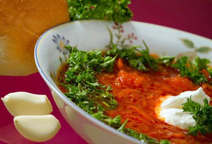 Polévka s červenou řepou a zelím ozdobená petrželkou a zakysanou smetanou v hlubokém talíři.