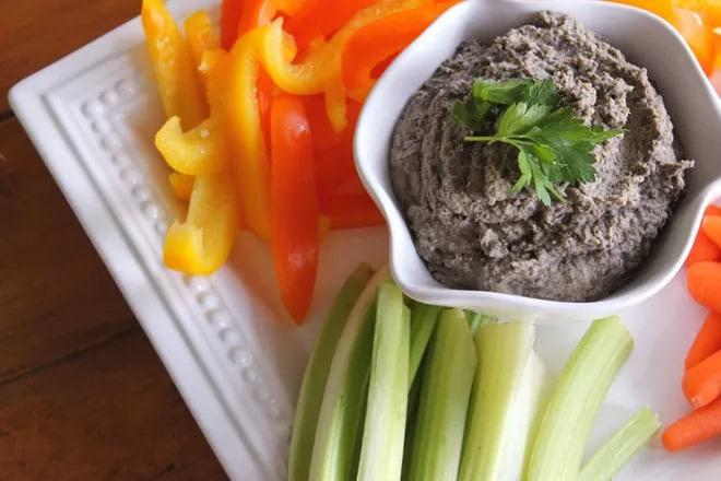 Dip z černé čočky s bylinkou na vrchu v servírovací misce obložený paprikou a další zeleninou.
