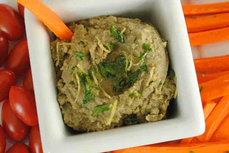 Pomazánka z čočky, citronu a bylinek v servírovací misce, která je obložená zeleninou.