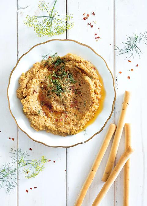 Dip z červené čočky s javorovým sirupem posypaná bylinkami v servírovací misce s tyčinkami.