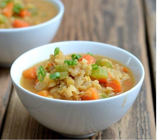 Luštěninová polévka se zeleninou v bílé misce.