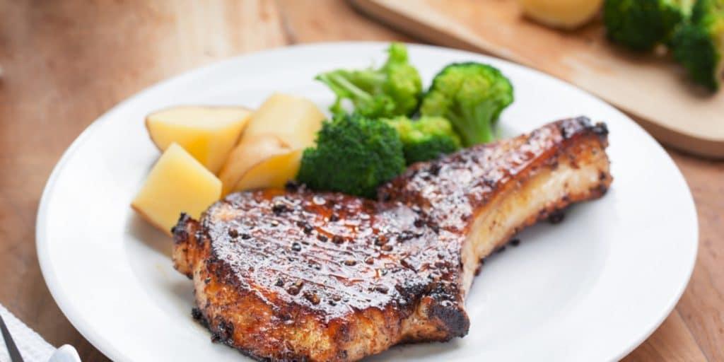 Vepřové s bramborami a brokolicí na talíři.