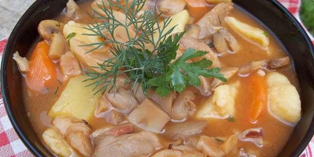 Houbová polévka se zeleninou a bylinkami v tmavé misce.