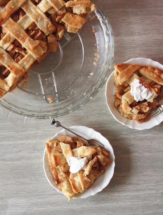 Jablečný koláč s mřížkou ve skleněné formě s vedle servírovanými kousky koláče na talířcích s vidličkou.