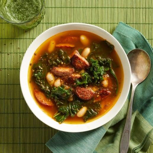 zeleninová polévka s klobásou a fazolemi v bílé misce se lžičkou vedle