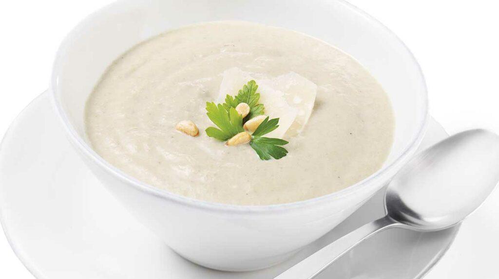 Rozmixovaná krémová polévka z hub v bílé misce se sýrem, oříšky a bylinkami.